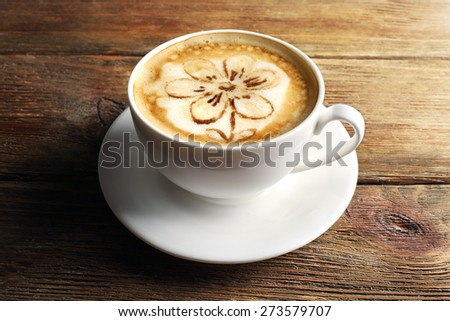 Cup of coffee latte art on wooden background - stock photo