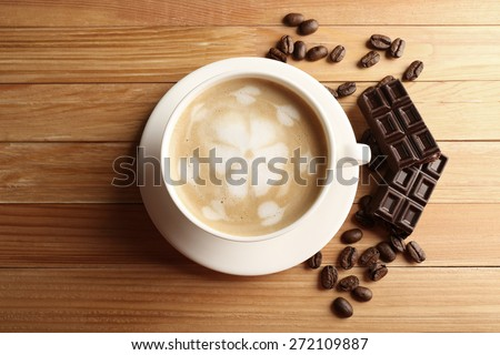 Cup of coffee latte art with grains and chocolate bar on wooden table, top view - stock photo