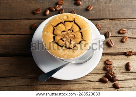 Cup of coffee latte art with grains on wooden background - stock photo