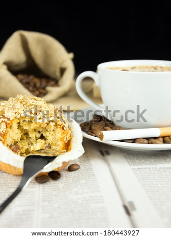 Cup of coffee, muffin and a  cigarette arranged on a newspaper - stock photo
