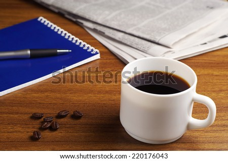 Cup of coffee, newspaper and notepad on wooden table - stock photo