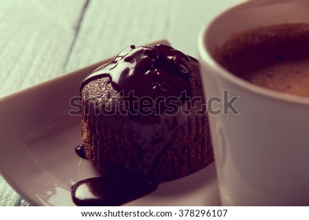 Cup of coffee on a plate next to a chocolate crunches muffin on a wooden table, top view - stock photo