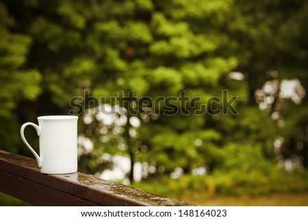 Cup of coffee on a rainy day in nature - stock photo