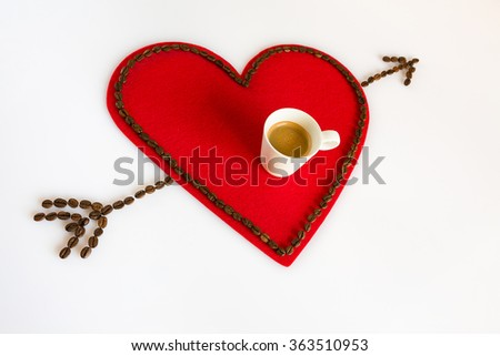 Cup of coffee on a red felt heart with coffee beans around and arrow in diagonal - stock photo