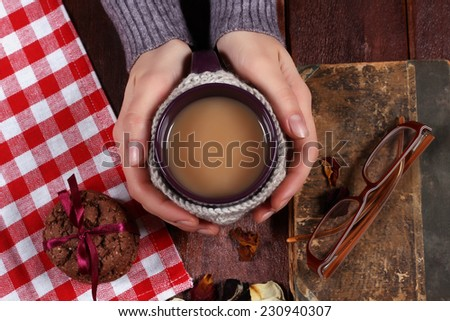 Cup of coffee on a table with her hands by women. Her hands, clasping a cup of coffee. Cup with knit cover. Mug in a knitted cover. The concept of romance and hanging out with a book - stock photo