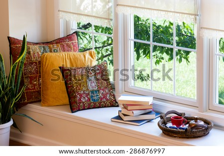 Cup of Coffee on a Tray, Piled Books and Square Pillows at the Reading Corner Inside the House. - stock photo