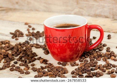 Cup of coffee on a wooden table with coffee beans. - stock photo