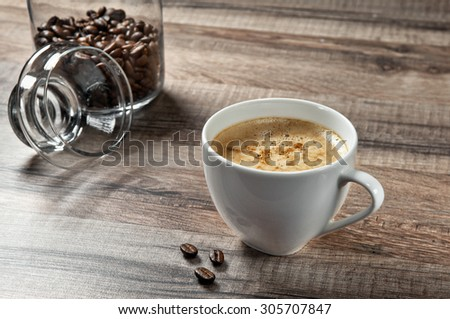 cup of coffee on a wooden table with coffee beans closeup. Top view. Free space for text. Copy space. - stock photo