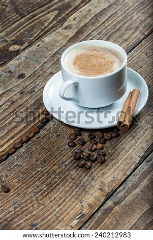 Cup of coffee on amid whole coffee beans with cinnamon - stock photo