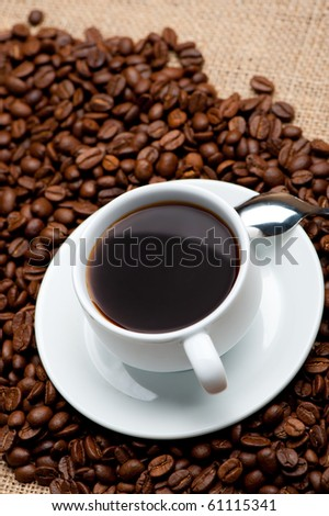 Cup of coffee on coffee grains. A hot drink - stock photo