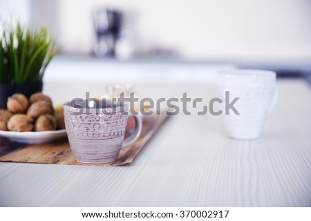 Cup of coffee on cotton napkin in the kitchen, close up - stock photo