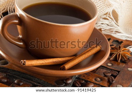 Cup of coffee on grange a background, coffee grains and cinnamon - stock photo