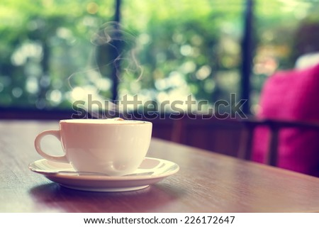 Cup of coffee on table in cafe Morning light , vintage or retro color toned  - stock photo