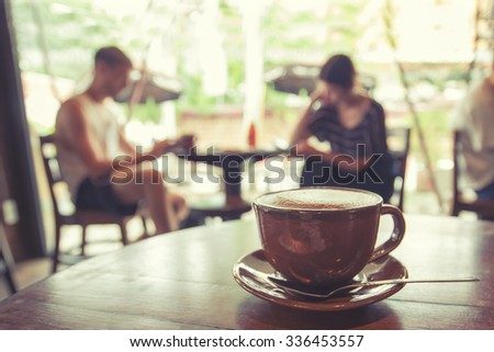 Cup of coffee on table in cafe with people retro instagram effect - shallow depth of field - stock photo