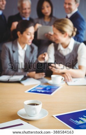 Cup of coffee on table in conference room and businesspeople working in background - stock photo