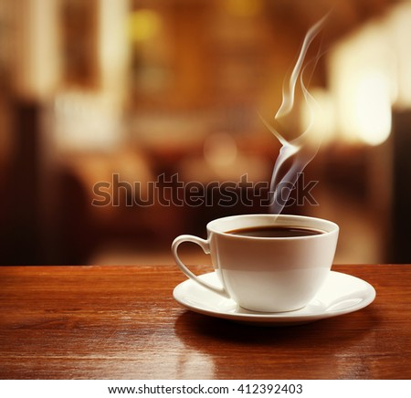 Cup of coffee on table on blured cafe background - stock photo