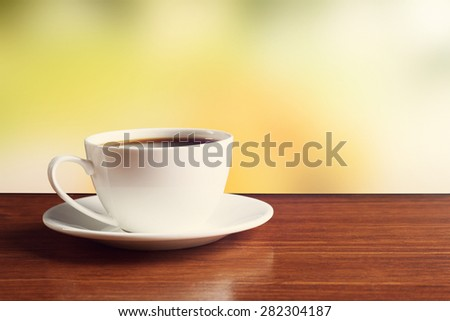 Cup of coffee on table on bright background - stock photo