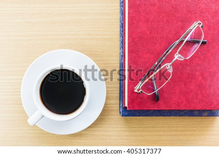 Cup of coffee on wood table and glasses put on red book - stock photo