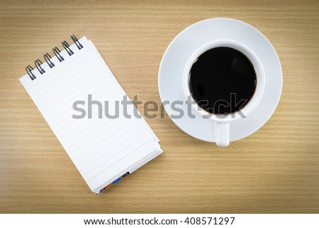 Cup of coffee on wood table and notepad - stock photo