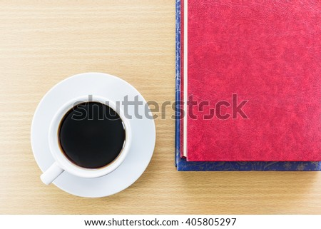 Cup of coffee on wood table and red book - stock photo