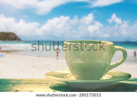 cup of coffee on wooden background over blue sky and sea on day noon light. - stock photo
