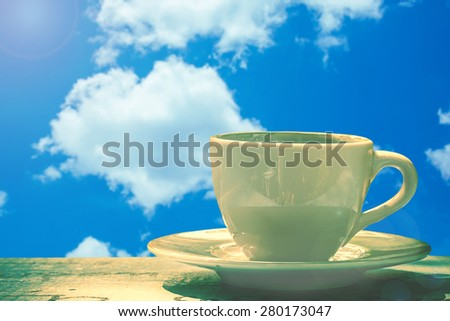 cup of coffee on wooden background over blue sky on day noon light. - stock photo