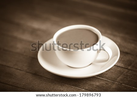 Cup of coffee on wooden table. Photo in old color image style. - stock photo