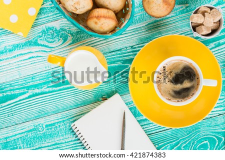 cup of coffee on yellow plate and yellow milk jug cane sugar, notebook, pen, cakes, teaspoon on turquoise colored wooden table with yellow napkin at polka dots top view - stock photo