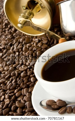 cup of coffee, pot and gold grinder on beans - stock photo