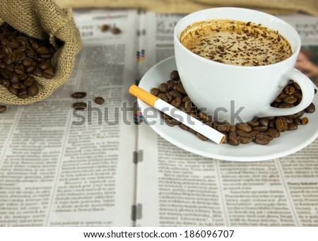 Cup of coffee, roasted beans and a cigarette arranged on a newspaper - stock photo