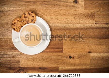 Cup of coffee served in porcelain saucer on wooden table. Shot from aerial view - stock photo