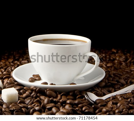 cup of coffee, spoon and beans isolated on black  background - stock photo