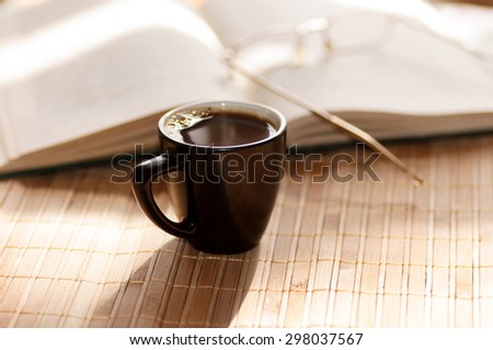 cup of coffee, standing next to an open book, on which lie glasses - stock photo
