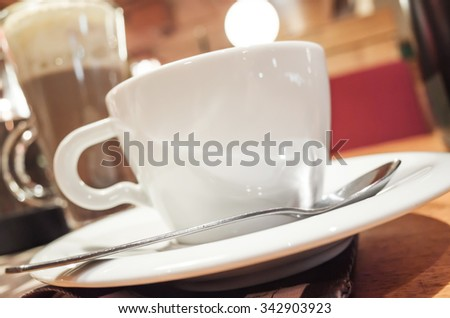 Cup of coffee stands on a table in cafeteria, photo with selective focus and shallow DOF - stock photo