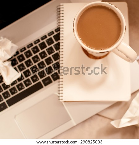 Cup of coffee staying on laptop with notebook closeup. Working process. Top view. - stock photo