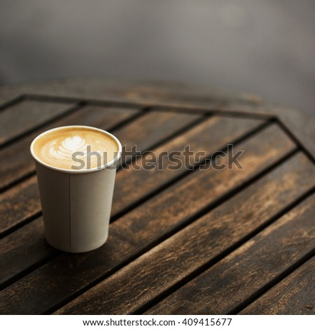 Cup of coffee to go on the wooden table with latte art. Street coffee - stock photo