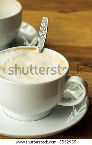 Cup of coffee with a teaspoon in the cup. The coffee has a creamy foam on top. There is another cup in the background on the table - stock photo