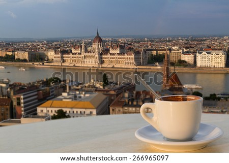 Cup of coffee with a view of the parliament building in Budapest (horizontal picture, the building in focus) - stock photo