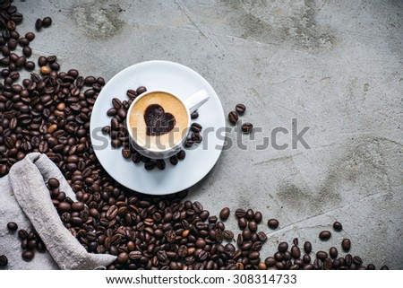 Cup of coffee with bag of roasted coffee beans - stock photo