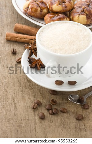 cup of coffee with beans and cakes on wood background - stock photo