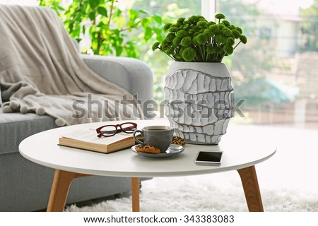 Cup of coffee with biscuits on table in room - stock photo