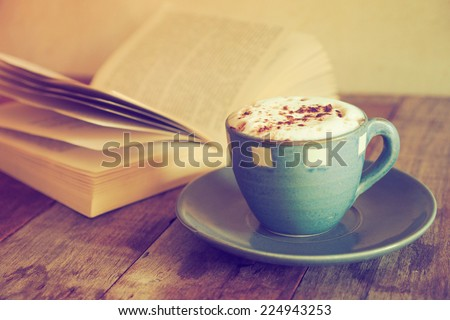 cup of coffee with book  in coffee shop vintage color - stock photo