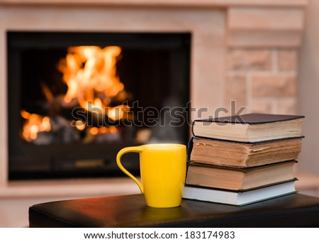 Cup of coffee with books on the background of the fireplace - stock photo
