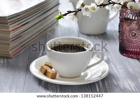 Cup of coffee  with branches of blooming cherry on wooden background - stock photo