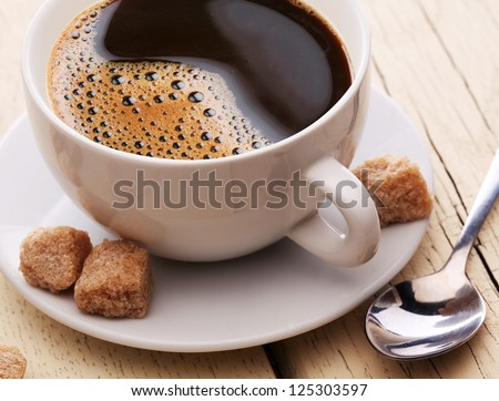Cup of coffee with brown sugar on a light wooden table. - stock photo