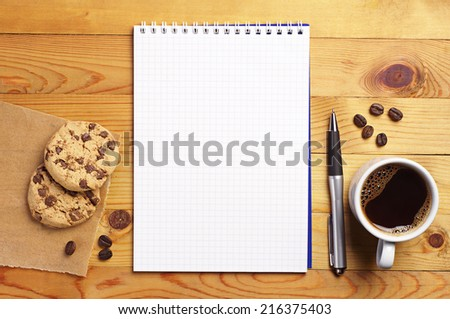 Cup of coffee with chocolate cookies and opened notepad on desk. Top view - stock photo
