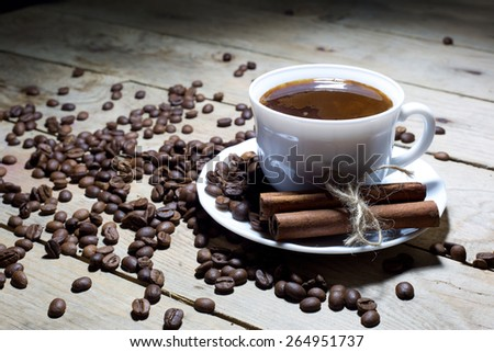 Cup of Coffee with Cinnamon and Coffee Beans on an Old Wooden Table - stock photo