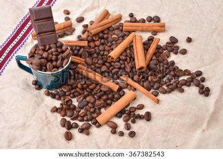 Cup of coffee with cinnamon sticks, bar of chocolate on vintage texture. Roasted coffee beans on jute background. Morning pleasures. Selective focus - stock photo
