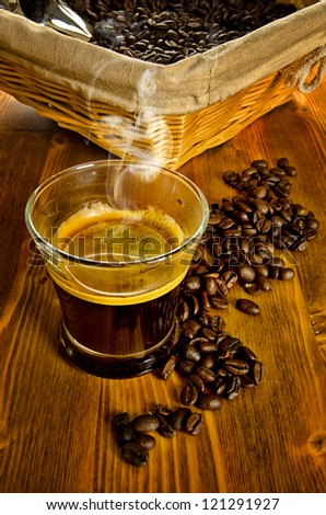 Cup of coffee with coffee beans and basket on background - stock photo