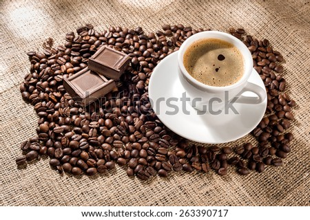 Cup of coffee with coffee beans and chocolate pieces on burlap background. - stock photo